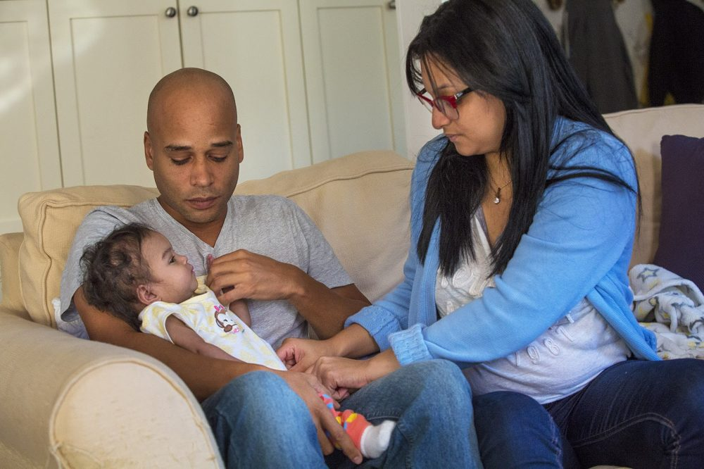 Andino hands Amaia, to father Kelvin Garcia to hold while she fixes Amaia's jumper. (Jesse Costa/WBUR)