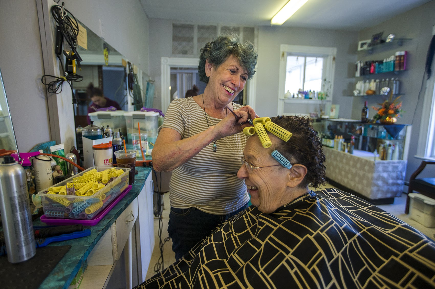 Judy Wilkins calls herself the poster child for a new type of cancertherapy called CAR-T. As she is having a laugh, Wilkins is putting hair rollers into Annina McCully's hair at her salon in Woburn. (Jesse Costa/WBUR)