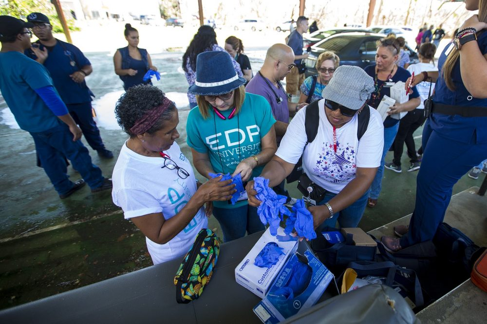 Volunteer HIMA health workers grab Nitrile exam gloves preparing for their trips out to help victims of Hurricane Maria in Punta Santiago. (Jesse Costa/WBUR)