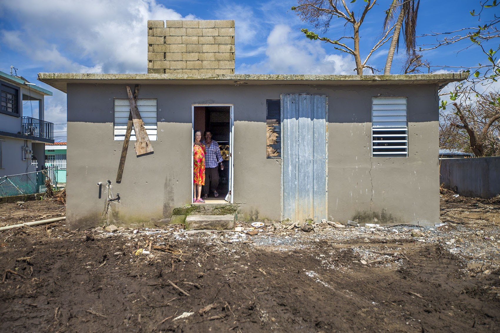 A man and a woman look outside their beaten and weathered house in Punto Santiago where Hurricane Maria first made landfall. (Jesse Costa/WBUR)