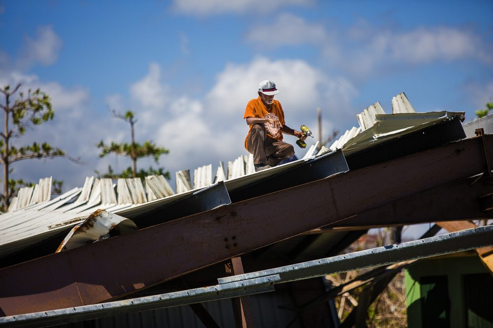 A worker removing the bolts of a roof of a metal structure that had collapsed during Hurricane Maria. (Jesse Costa/WBUR)