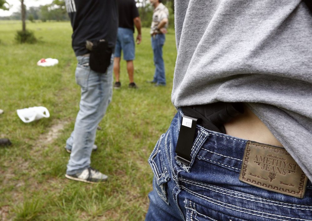 In this April 2016 photo, Crestview Baptist Church member Courtney Davis shows where she holsters her concealed firearm while another participant uses a hip holster as they await their turn to shoot during the live fire portion of a enhanced concealed carry class in Petal, Miss. (Rogelio V. Solis/AP)