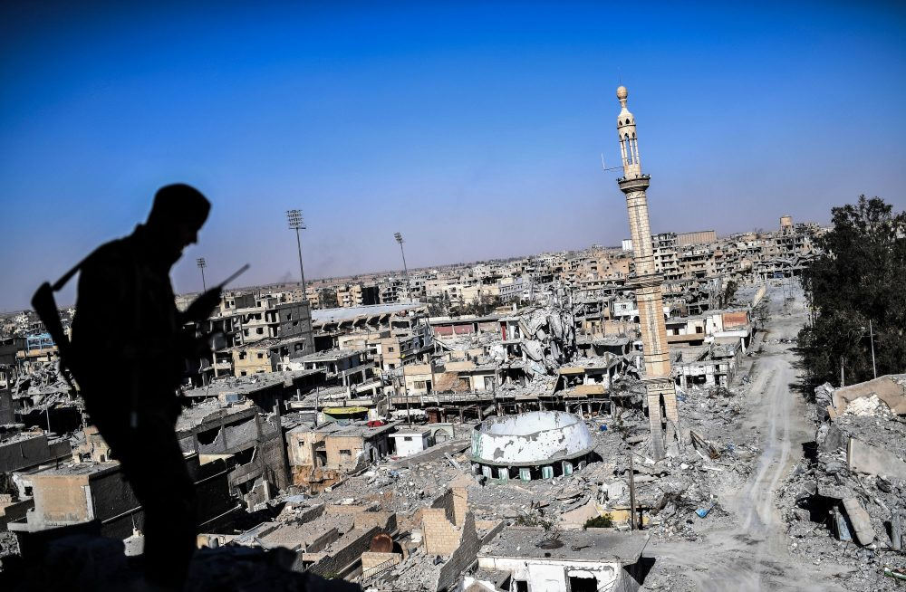 A member of the Syrian Democratic Forces (SDF), backed by U.S. special forces, talks on the radio near Raqqa's stadium as they clear the last positions on the frontline on Oct. 16, 2017, in the Islamic State group jihadists' crumbling stronghold. (Bulent Kilic/AFP/Getty Images)