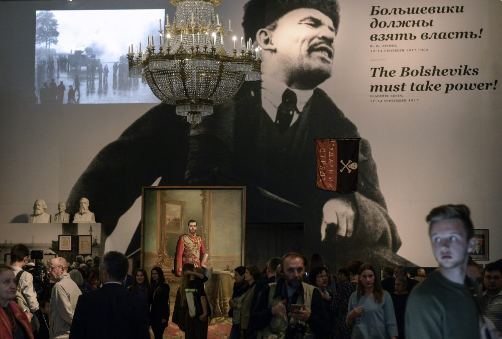 "People gather by a portrait of the last Russian tsar Nicholas II and a huge image of the Soviet Union founder Vladimir Lenin during the opening of the exhibition entitled ""The Winter Palace and the Hermitage in 1917. History was made here"" at the State Hermitage Museum in Saint Petersburg on Oct. 25, 2017. (Olga Maltseva/AFP/Getty Images)"