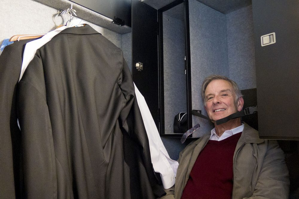 Assistant principal bassist Lawrence Wolfe climbs inside his gigantic travel case and jokes that it's the size of a coffin. (Andrea Shea/WBUR)