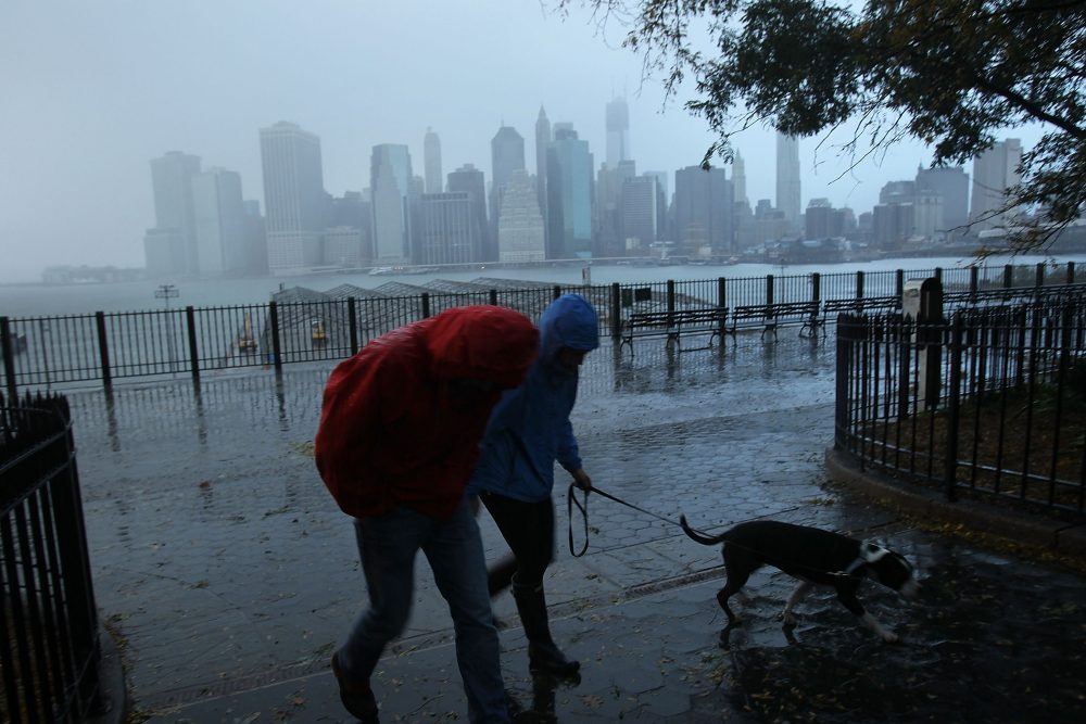 A couple walks in the rain as a darkened Manhattan is viewed after much of the city lost electricity due to the affects of Hurricane Sandy on Oct. 30, 2012 in New York. (Spencer Platt/Getty Images)