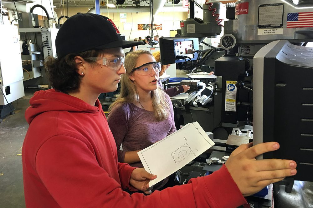 Sophomore Caleb Simmler and senior Michelle Yitts make plastic tic-tac-toe pieces on a three-axis milling machine. (Lynn Jolicoeur/WBUR)