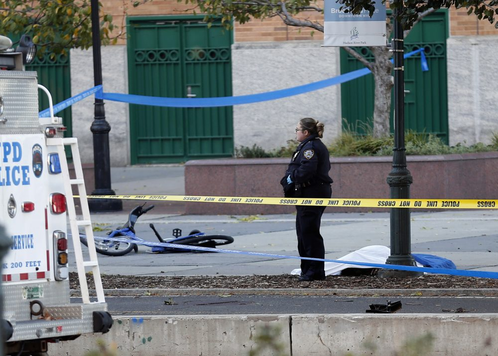 A New York Police Department officer stands next to a body covered under a white sheet near a mangled bike along a bike path Tuesday Oct. 31, 2017, in New York. (Bebeto Matthews/AP)