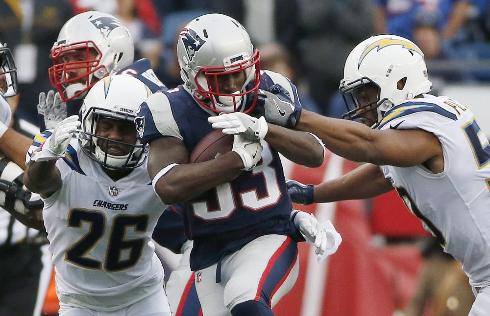 New England Patriots running back Dion Lewis carries the ball against Los Angeles Chargers cornerback Casey Hayward (26) and inside linebacker Hayes Pullard, right, during the second half of Sunday's game in Foxborough. (Michael Dwyer/AP)