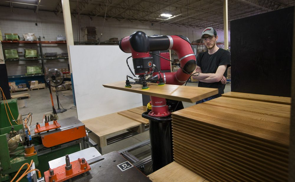"Brandon Correia, 23, is essentially the robot ""supervisor"" at Moduform, a Fitchburg-based furniture-maker. (Jesse Costa/WBUR)"