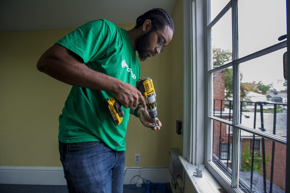 Aaron Ennis installs a window shade during one of his jobs at the Tellus Institute in Cambridge. (Jesse Costa/WBUR)