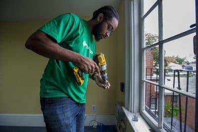 Aaron Ennis installs a window shade during one of his jobs at the Tellus Institute in Cambridge. (Jesse Costa/WBUR)