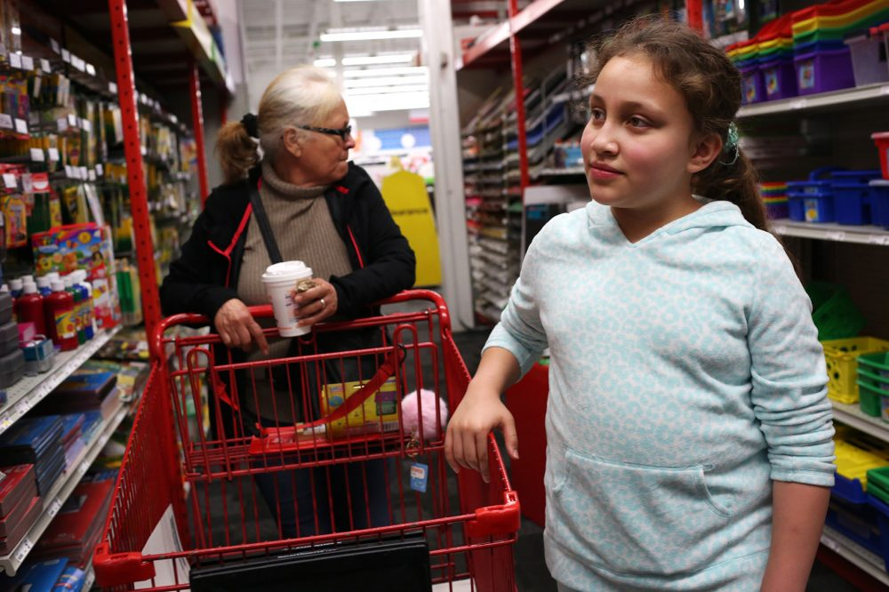 Mellanie Rodriguez, Francisco Rodriguez's 10-year-old daughter, goes shopping for school supplies with her grandmother, Jesus Rodriguez, on Saturday. (Hadley Green for WBUR)