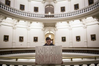 "Jacob Rubio holds a sign that reads ""We will overcome,"" in the rotunda of the state Capitol shortly after the Electoral College cast their vote in Austin, Texas, Monday, Dec. 19, 2016. (Tamir Kalifa/AP)"