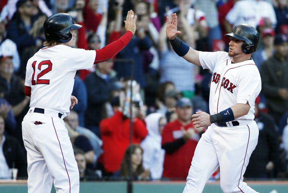 Boston Red Sox's Christian Vazquez and Brock Holt (12) celebrate after scoring on a two-run double by Rafael Devers during the fourth inning of a baseball game against the Houston Astros in Boston, Sunday, Oct. 1, 2017. (AP Photo/Michael Dwyer)