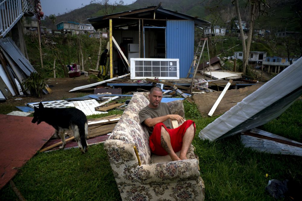 """Angel Rodriguez poses next to his belongings in front of his house, destroyed by Hurricane Maria, in the San Lorenzo neighborhood of Morovis, Puerto Rico, Saturday, Sept. 30, 2017. Rodriguez said that it rained and rained. """"I was really afraid on the night of the hurricane. But the important thing is to be alive,"""" he said. (Ramon Espinosa/AP)"""