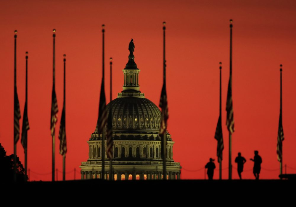 The U.S. Capitol dome backdrops flags at half-staff in honor of the victims killed in the Las Vegas shooting as the sun rises on Tuesday, Oct. 3, 2017, at the foot of the Washington Monument on the National Mall in Washington. (Manuel Balce Ceneta/AP)