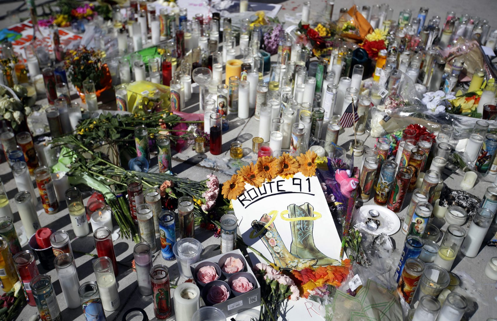 Flowers and candles are left at a makeshift memorial site on Las Vegas Boulevard on Tuesday, Oct. 3, 2017, in Las Vegas. A gunman opened fire on an outdoor music concert on Sunday killing dozens and injuring hundreds. (Chris Carlson/AP)