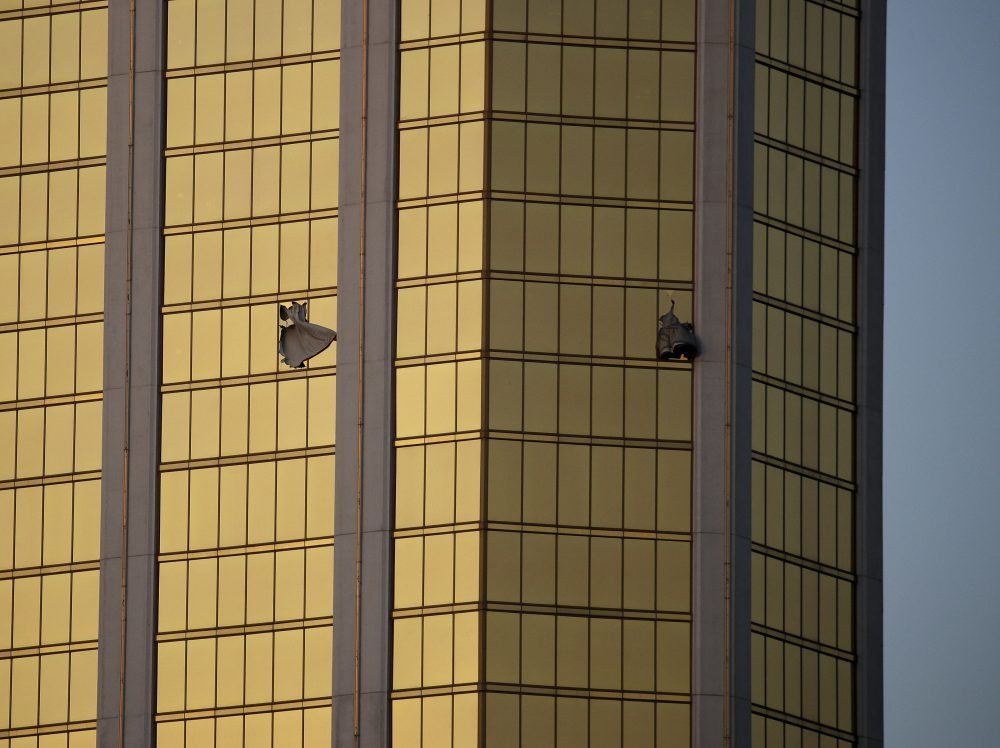 In this Oct. 2 file photo, drapes billow out of broken windows at the Mandalay Bay resort and casino on the Las Vegas Strip, following a mass shooting at a music festival. (John Locher/AP)