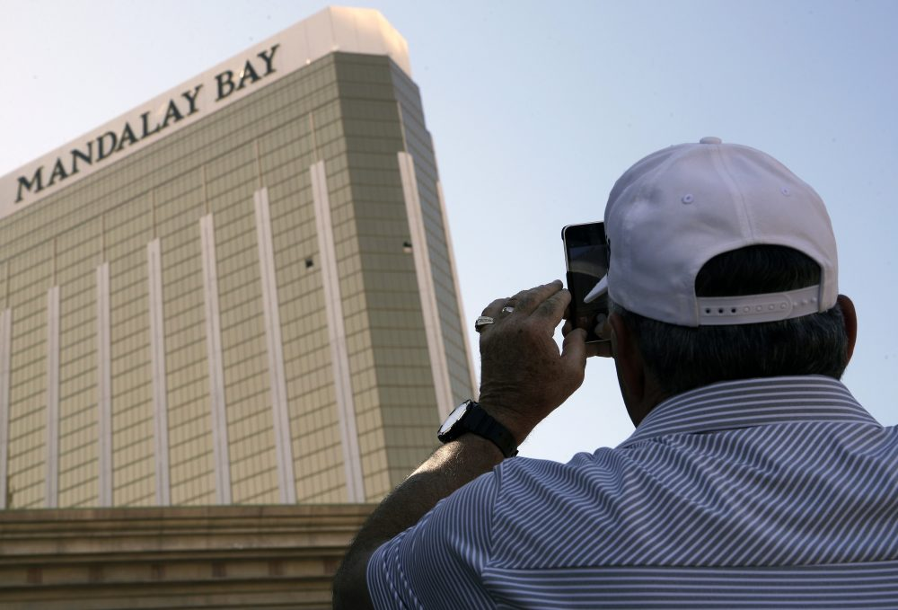 A tourist takes a photo of the broken out windows at the Mandalay Bay hotel on Wednesday, Oct. 4, 2017, in Las Vegas. A gunman opened fire on an outdoor music concert on Sunday killing dozens and injuring hundreds, from the windows. (John Locher/AP)