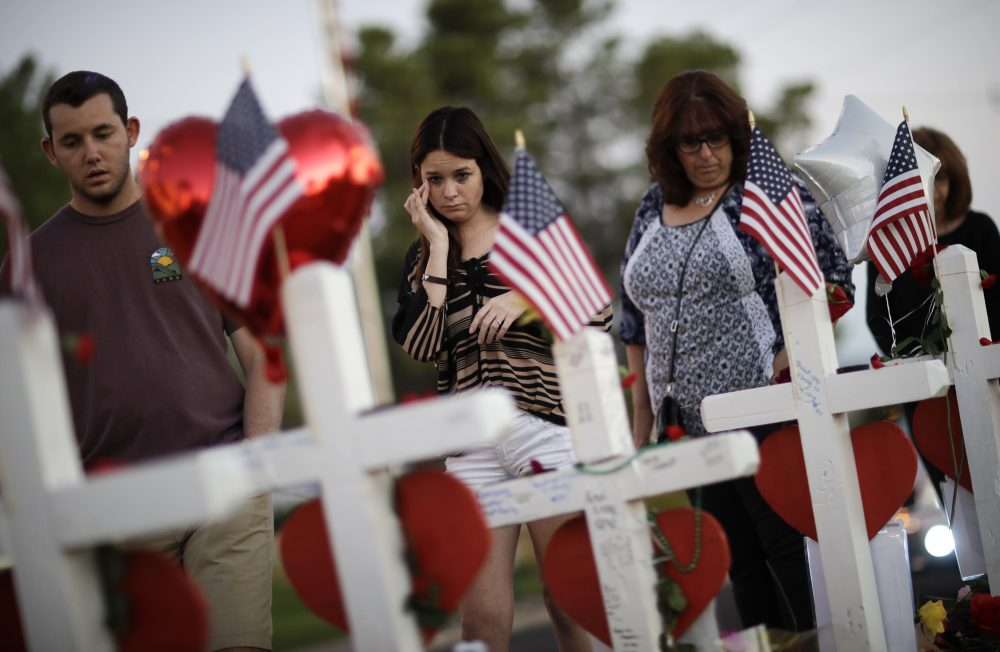 People visit a makeshift memorial Friday, Oct. 6, 2017, for victims of a mass shooting in Las Vegas. Stephen Paddock opened fire on an outdoor music concert on Sunday killing dozens and injuring hundreds. (John Locher/AP)