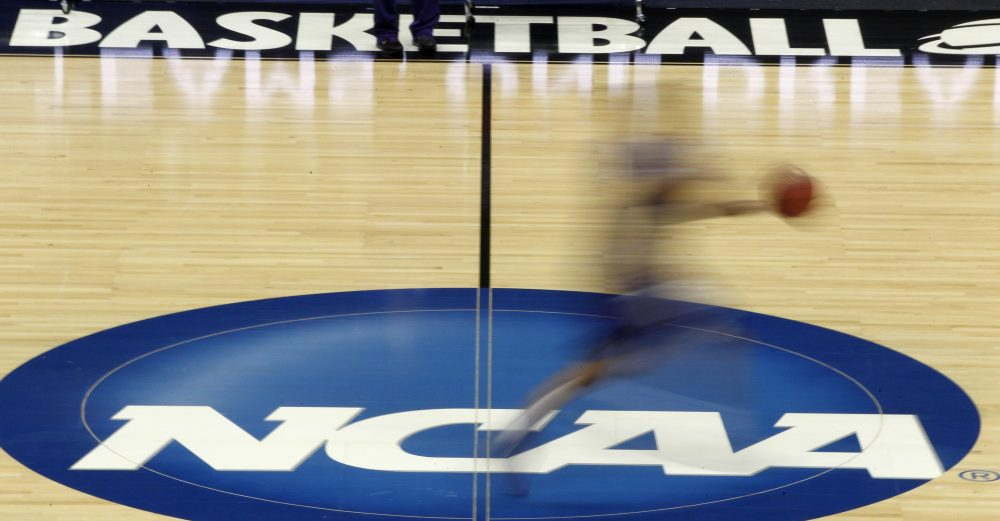 In this March 14, 2012, file photo, a player runs across the NCAA logo during practice in Pittsburgh before an NCAA tournament college basketball game. (Keith Srakocic/AP)
