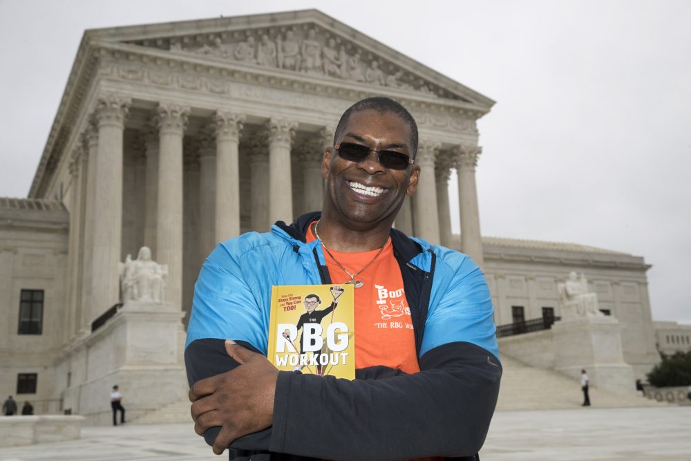 "Bryant Johnson, personal trainer for Justice Ruth Bader Ginsburg, poses in Washington with his new book, ""The RBG Workout: How She Stays Strong ... and You Can Too!"" (J. Scott Applewhite/AP)"