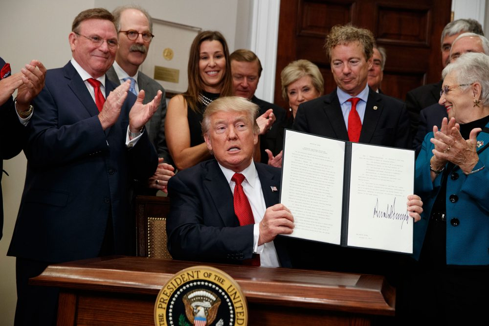 President Trump shows an executive order on health care that he signed in the Roosevelt Room of the White House on Oct. 12. Dave Ratner is second from left, behind Trump. (Evan Vucci/AP)