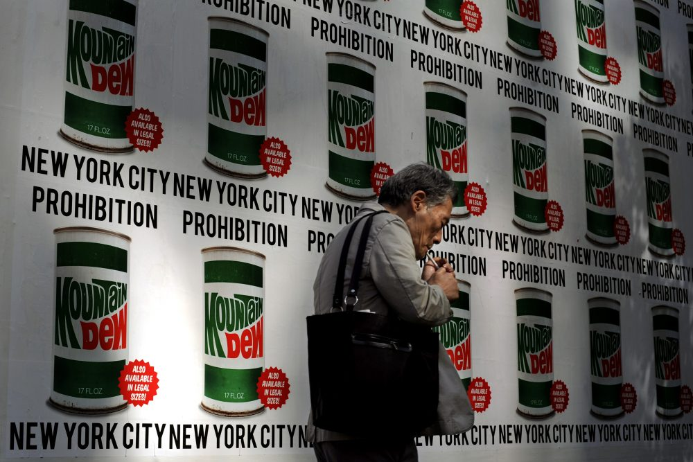 A man lights a cigarette as he walks past an advertisement created in collaboration with Mountain Dew and New York Art Department, Thursday, Sept. 13, 2012, on 13th Street in New York. (Jeffrey Furticella/AP)