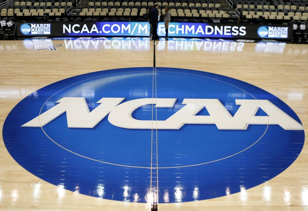 In this March 18, 2015 photo, the NCAA logo is at center court for the NCAA college basketball second and third round games.  The NCAA and 11 major athletic conferences announced Friday, Feb. 3, 2017,  they have agreed to pay $208.7 million to settle a federal class-action lawsuit filed by former college athletes who claimed the value of their scholarships was illegally capped. (AP Photo/Keith Srakocic, File)