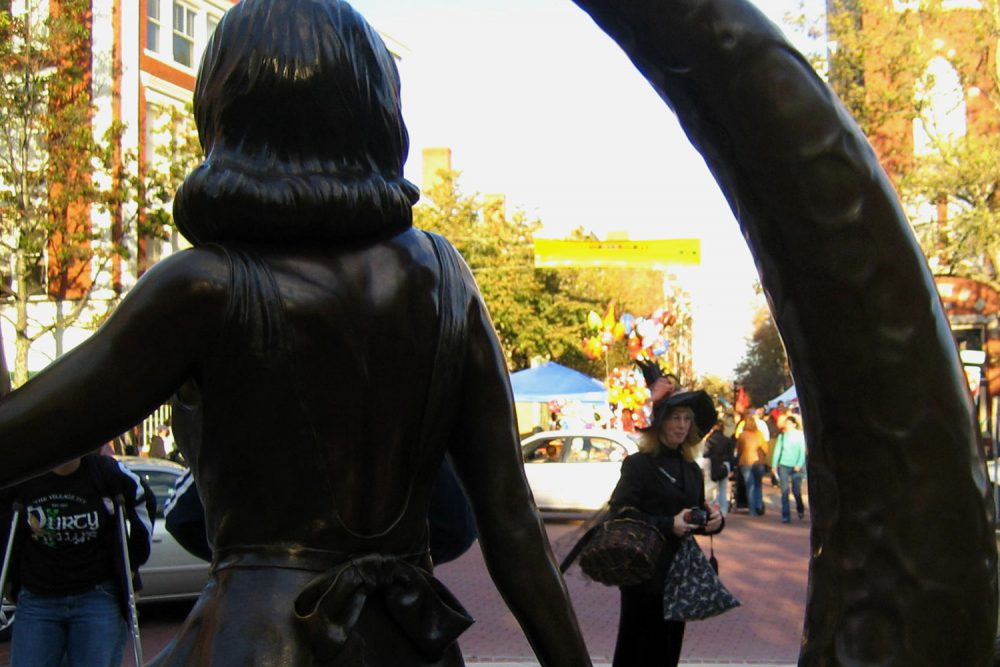 """A woman dressed as a witch is framed by a statue in downtown Salem of Samantha Stevens, the witch on the TV show """"Bewitched."""""""