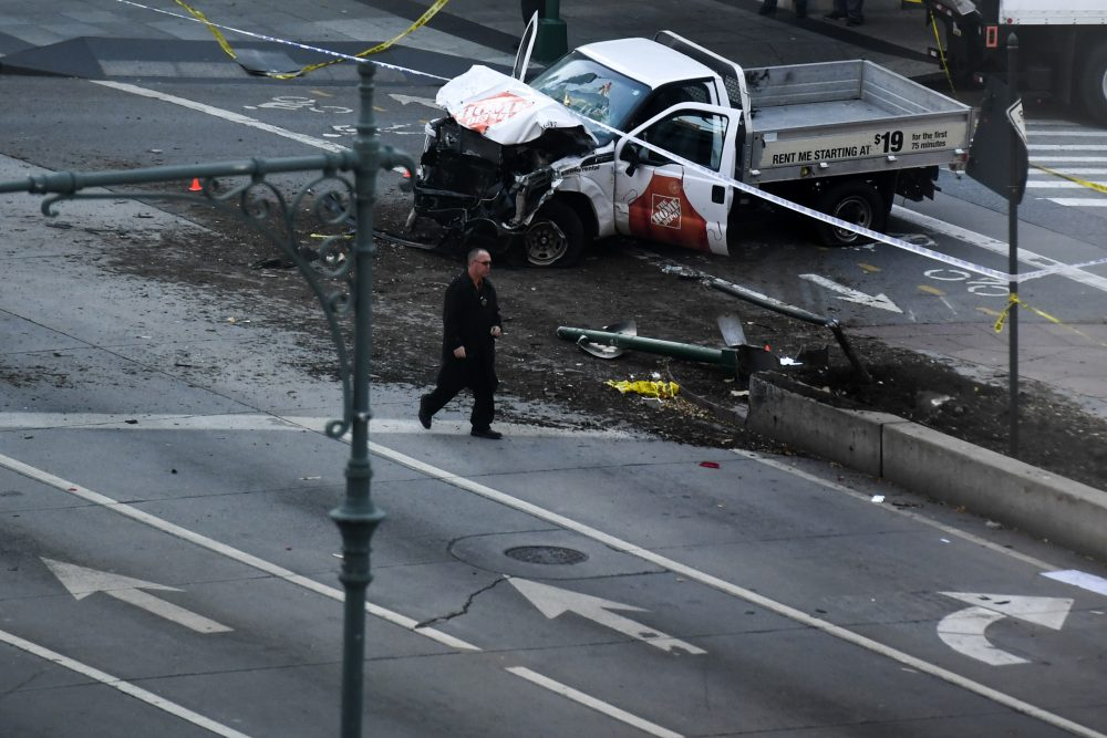 """An investigator walks past a crashed pickup truck following an incident in New York on Oct. 31, 2017. A pickup driver killed eight people in New York on Tuesday, mowing down cyclists and pedestrians, before striking a school bus in what officials branded a """"cowardly act of terror."""" (Don Emmert/AFP/Getty Images)"""