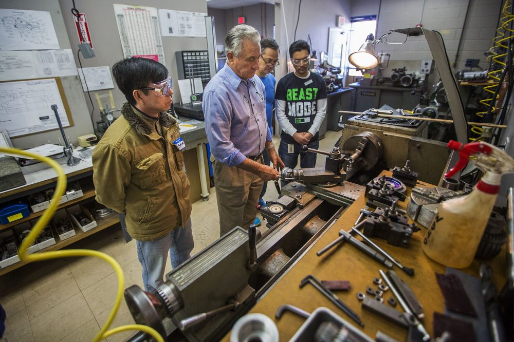 Cosmo Pasciuto shows students how to operate a lathe at the Center for Manufacturing Technology at Custom Machine in Woburn. (Jesse Costa/WBUR)