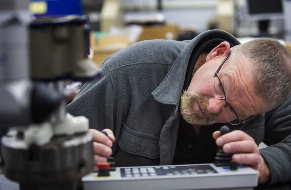 Mike Twombly uses a sophisticated tool to precisely measure the diameter of a part that has been recently fabricated at Custom Machine. (Jesse Costa/WBUR)