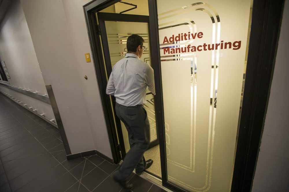 Chris DiBiasio, group leader for advanced manufacturing, walks into the Additive Manufacturing facility at Draper. (Jesse Costa/WBUR)