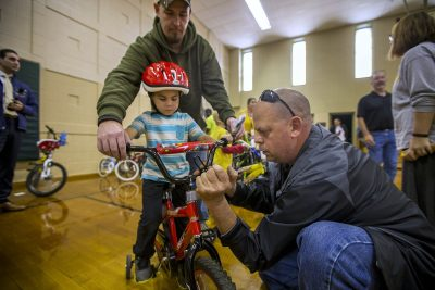 Five-year-old Christopher watches as Bob Charland, right, adjusts the handlebars of the bicycle he just received through the Pedal Thru Youth program at the Stefanik School in Chicopee. (Jesse Costa/WBUR)