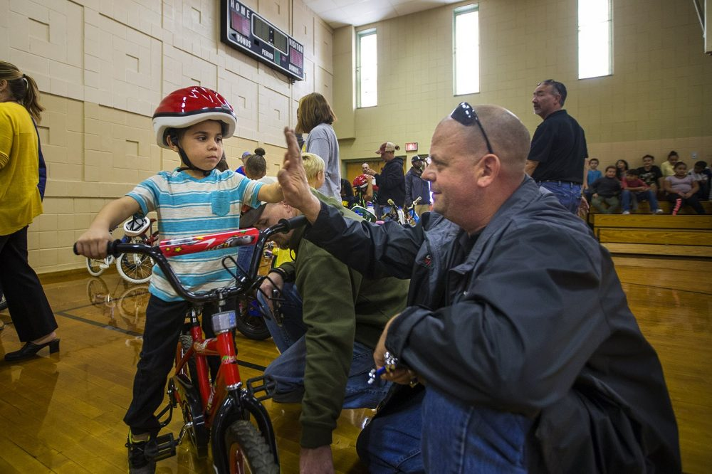 Five-year-old Christopher and Bob Charland celebrate with a high five after adjustments are made to his new bike so he can ride it. (Jesse Costa/WBUR)