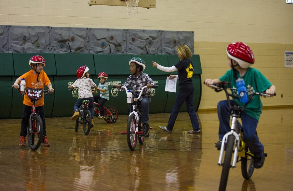 Children take test rides on their newly acquired bicycles in the gymnasium of the Stefanik School. (Jesse Costa/WBUR)