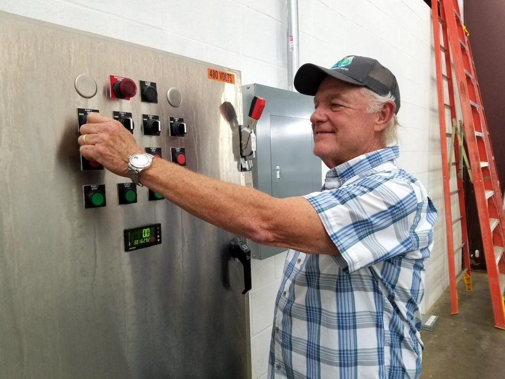 Jim Bruner flips the switch on a pump at Planet H20. (Chas Sisk/WPLN)