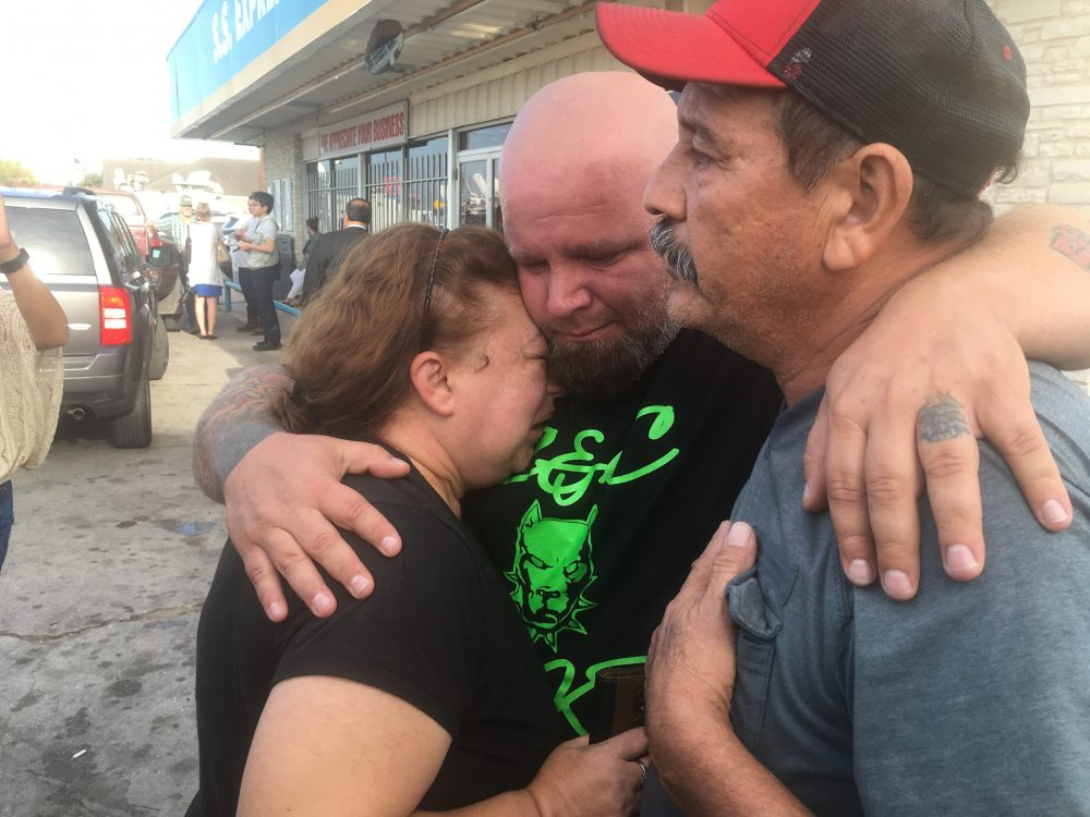 Lorenzo Flores and Terri Smith are comforted by a friend. Flores and Smith learned their friend Joann Ward and two of her children were killed in the shooting. (Joey Palacios/Texas Public Radio)
