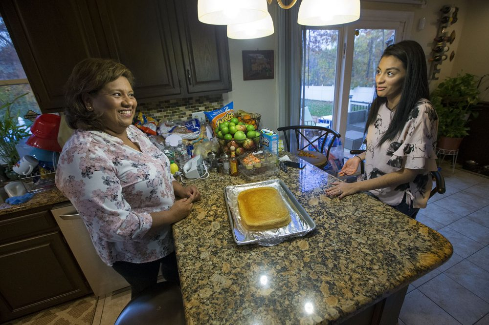 Irma Flores, right, and her daughter, Gabriela Portillo-Perez, discuss the recipe for a tres leches cake they're making to surprise Portillo-Perez's husband. (Jesse Costa/WBUR)