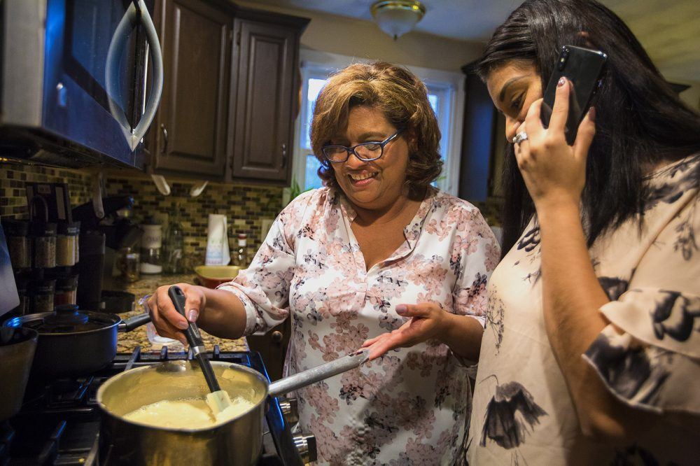 As Irma Flores stirs milk in a pan, her daughter Gabriela Portillo-Perez speaks with her grandmother Isabel on the phone in El Salvador. The Trump administration said Monday it woul dbe ending(Jesse Costa/WBUR)