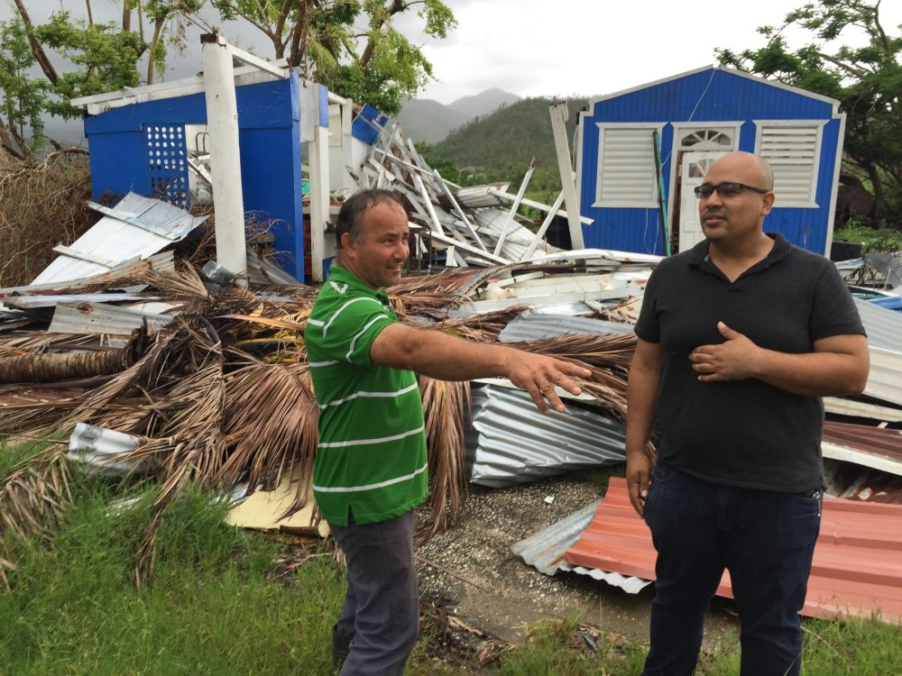 Jan Carlo Perez (right) talks with a neighbor this month in front of a house demolished in Patillas, Puerto Rico, by Hurricane Maria in September. (Tim Padgett/WLRN)