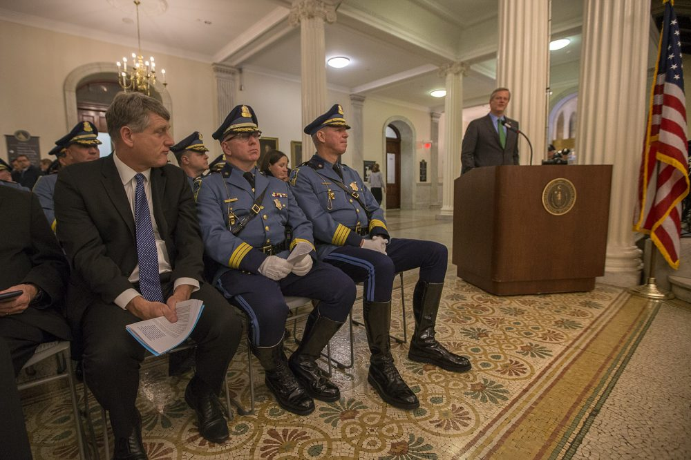 From left: State Public Safety Secretary Daniel Bennett, Lieutenant Colonel Francis Hughes and Colonel Richard McKeon listen while Gov. Charlie Baker speaks during the Massachusetts State Police Fall Awards Ceremony at the State House. (Jesse Costa/WBUR)