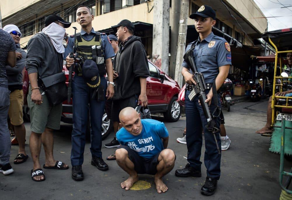 An alleged drug dealer is captured by police officers after a drug buy-bust operation on a slum area in Manila on Sept. 28, 2017. (Noel Celis/AFP/Getty Images)