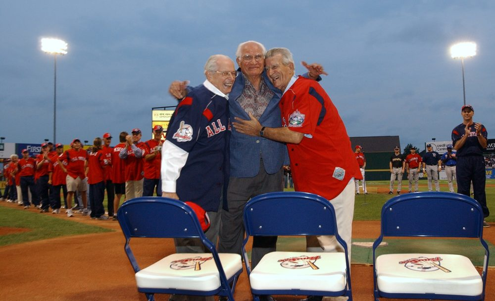 Baseball great Bobby Doer, center, hugs fellow baseball greats Dom DiMaggio, left, and Johnny Pesky as celebrity and Triple-A home run derby participants stand behind them on July 12, 2004, at McCoy Stadium in Pawtucket, R.I. (Victoria Arocho/AP)