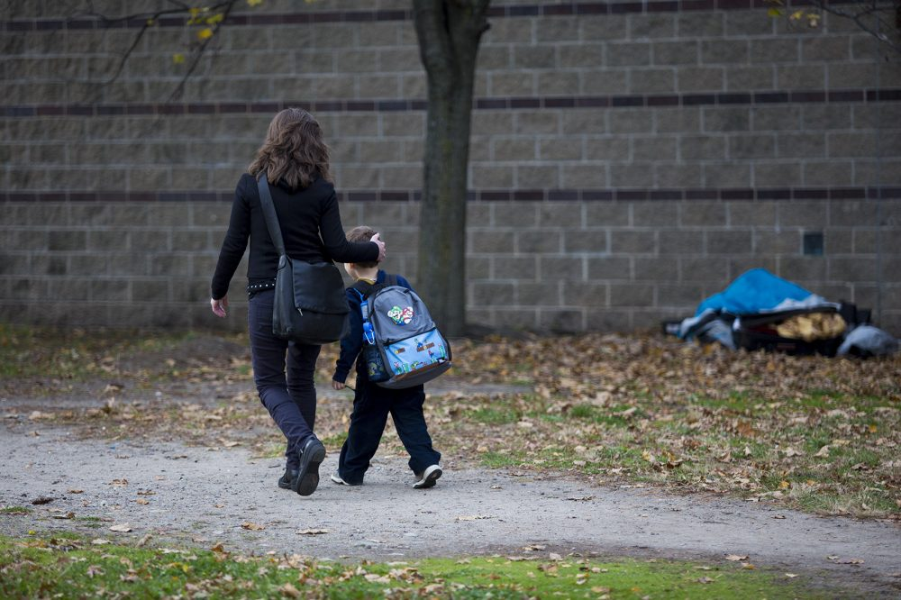 Caroline Toth-Bernstein walks with her 6-year-old son Oscar past a broken down tent and suitcase in a vacant lot they walk through every day to go to and from the Orchard Gardens K-8 Pilot School. (Jesse Costa/WBUR)