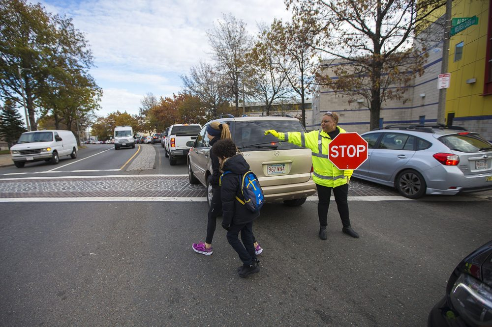 Crossing guard Karen Perry ushers an Orchard Gardens parent and her child across Melnea Cass Boulevard through busy traffic. (Jesse Costa/WBUR)