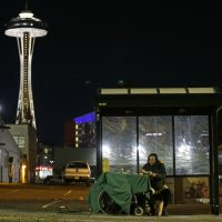 In this Oct. 30, 2017 photo, Dave Chung, who says he has been homeless for five years on the streets of California and Washington state, eats a meal before bedding down in a bus shelter in view of the Space Needle in Seattle. Chung says he has been offered shelter many times, but chooses to remain outside due to the living conditions in homeless shelters and conflicts he has with other people. (Ted S. Warren/AP)