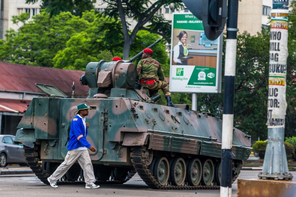 "A man walks past an armoured personnel carrier that stations by an intersection as Zimbabwean soldiers regulate traffic in Harare on Nov. 15, 2017. Zimbabwe's military appeared to be in control of the country on Nov. 15 as generals denied staging a coup but used state television to vow to target ""criminals"" close to President Mugabe. (AFP/Getty Images)"